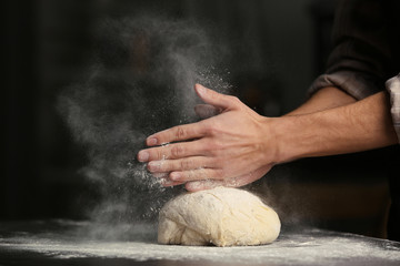 Male hands clapping and sprinkling flour over dough on black background