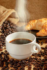 Hot coffee cup and breakfast baked croissants on wooden background