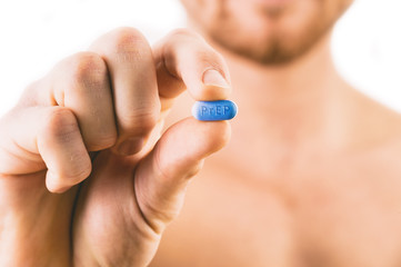 Man holding a pill used for Pre-Exposure Prophylaxis (PrEP) to p