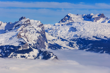 Summits of the Swiss Alps rising from sea of fog - wintertime view from Mt. Fronalpstock in the Swiss canton of Schwyz
