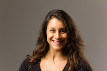 Young mixed race woman wearing a black t shirt and jeans stands in full face view while smiling at viewer