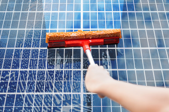 Person Cleaning Solar Panel
