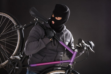 Person Wearing Balaclava Stealing A Bicycle