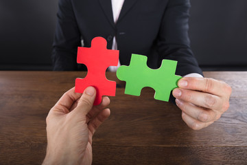 Two Businessmen Joining Jigsaw Pieces