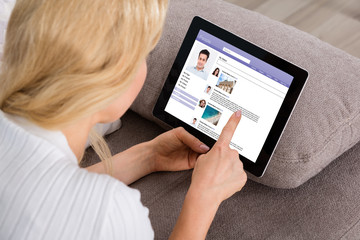 Woman Using Social Networking Site On Digital Tablet