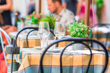 Summer empty open air restaraunt in Vatican city in Italy. Closeup wineglasses on the table