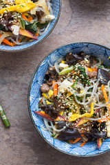 Japchae- Korean sweet potato noodle salad  in a blue bowl.