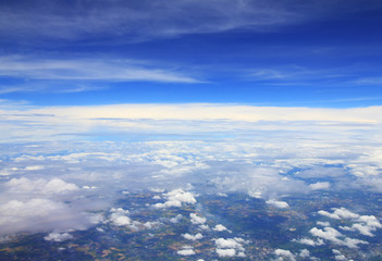 Aerial photo of land and clouds from above.