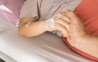 husband holding hand his wife in hospital