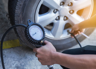 Close up mechanic inflating tire and checking air pressure with gauge pressure