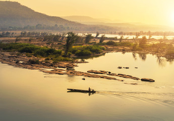 wooden fishing boat sailing in mekong river on sunrise at khongjiam district of thailand border of thailand and laos