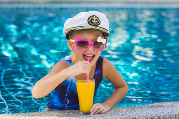 cheerful joyful girl in a sailor hat with a glass of juice in the pool on holiday