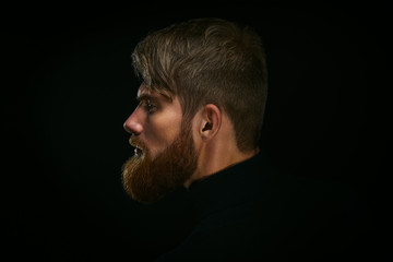 Portrait of young bearded man isolated at black background Guy w