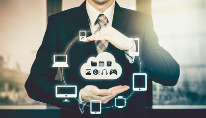 Businessman holding a cloud connected to many objects on virtual screen concept about the internet of things
