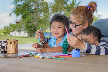 Asian family drawing picture on table