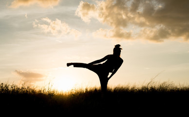 Women exercising in Meadow at sunset