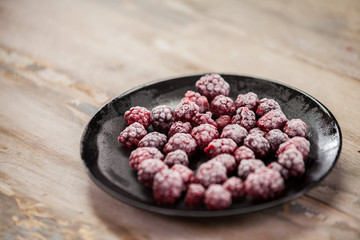 Frozen berries in bowls on wooden background. Selective focus.