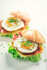 Tasty burger with bacon, eggs and cheese on white table