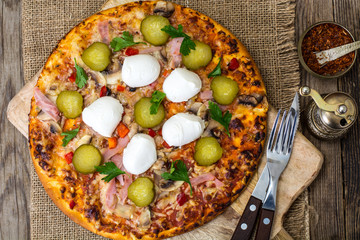 Pizza with ham, mushrooms, gherkin and mozzarella