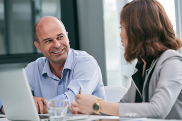 Waist-up portrait of smiling businessman looking at his female colleague while listening to her ideas in modern office