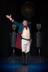 male actor in an old uniform coat and cocked hat posing against the backdrop of the scenery for the play