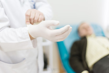 doctor, urologist wears medical gloves while patient waiting
