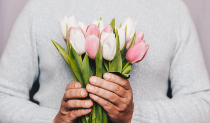 Man holding Bouquet of tulips in hand