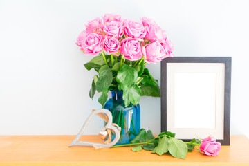 Violet fresh roses with heart and copy space on empty photo frame on wooden shelf