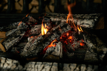 Closeup image of romantic vintage fireplace with flame from burning woods logs.Cozy sweet home concept.
