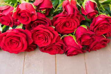 Dark Red buds of valentines day fresh roses border on gray wood