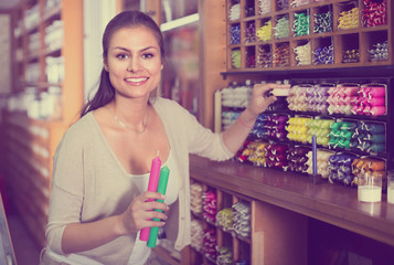 Positive woman shopping multicolored candles