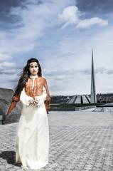 Girl in national dress standing in Tsitsernakaberd .