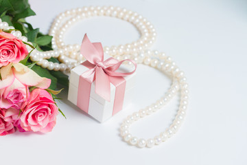 Gift box with pink ribbon with pearl jewellery and roses on white table