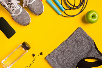 Fitness accessories on yellow background. Sneakers, bottle of water, headphones and sport top.