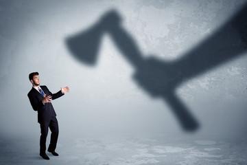 Businessman afraid of a huge shadow hand holding an axe concept