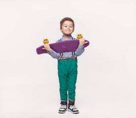 Stylish kid boy holding his birthday gift skateboard