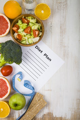 Food and sheet of paper with a diet plan on a  wooden table.