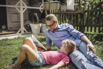 Father reading book with daughter in garden