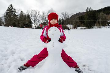 Little girl making snowman winter day