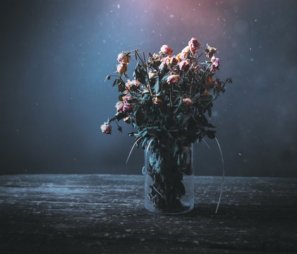 Dried bunch of roses in a vase on a wooden table on a black and blue background. Concept: dead flowers