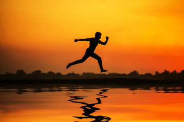 silhouette of man running and jumping on the beach near river.
