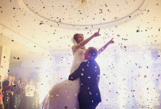 Happy beautiful newlyweds dancing in the restaurant