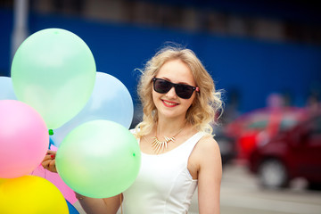 Close-up bright portrait of lovely young woman in sunglasses holding colorful balloons