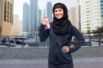 muslim woman with water bottle doing sport