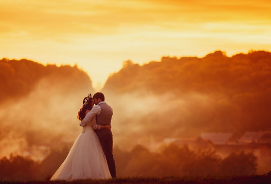 Bright orange sky and embracement of the newlyweds