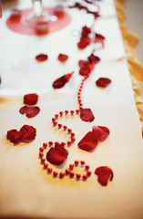 Red pearls and rose petals on the table