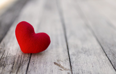Red heart over blurred wood background, selective focus, valentine background