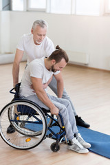 Helpful bearded father helping his disabled son in the gym