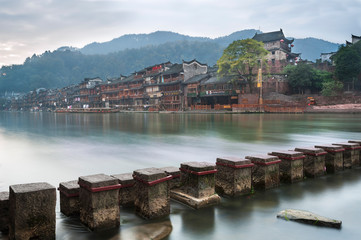 Stepping stones across the Tuojiang river with the North Gate Tower in the background in Fenghuang, Hunan Province, China
