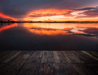 image of wooden floor in front of lake at sunset time,can be used for display or montage your products.
